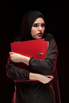 Porträt der jungen moslemischen frau, die das schwarze hijab hält ordner trägt, wie geheim halten