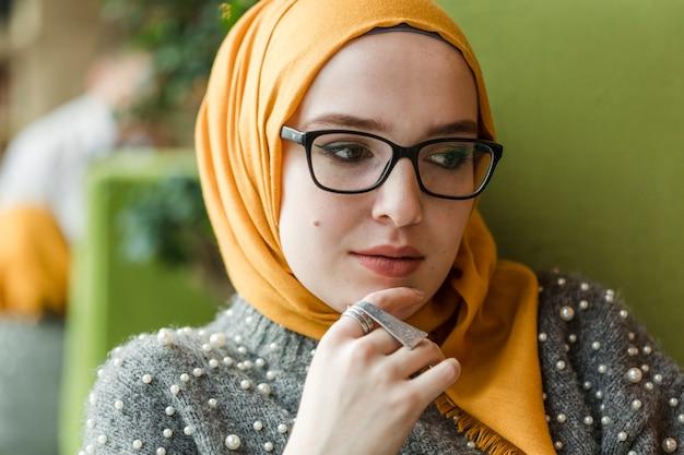 Porträt der jungen moslemischen frau, die weg schaut