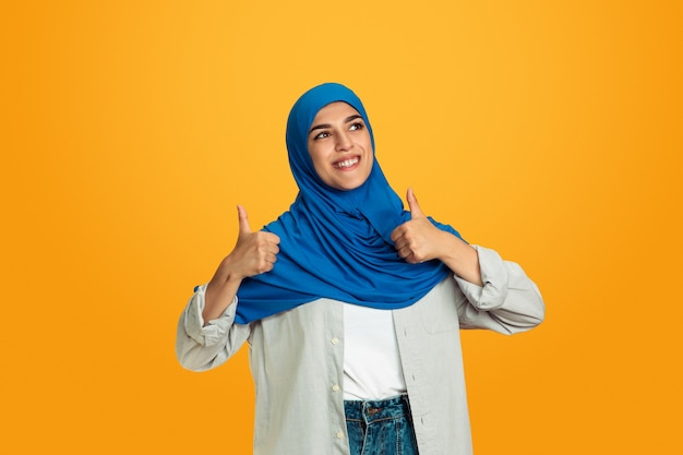Porträt der jungen muslimischen frau auf gelbem hintergrund