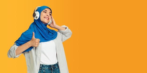 Porträt der jungen muslimischen frau auf gelber wand