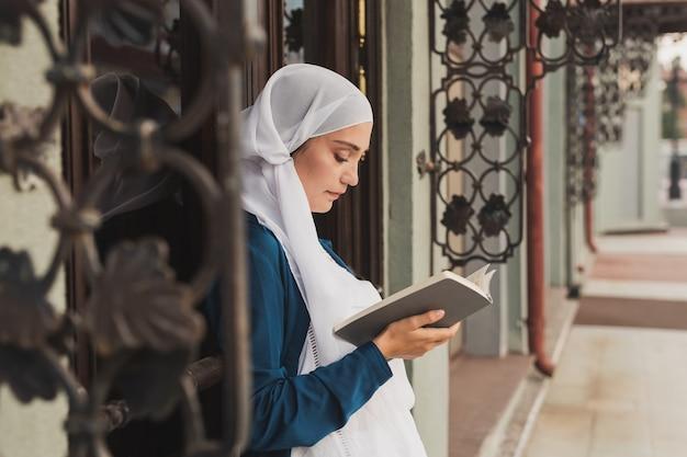 Porträt der jungen muslimischen frau mit hijab-lesebuch im freien
