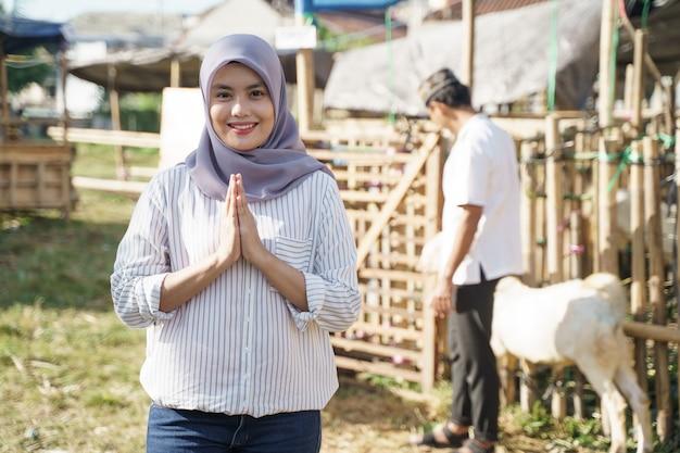 Porträt der jungen muslimischen frau mit ziege für idul adha qurban opfer