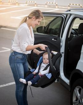 Porträt der jungen mutter, die autokindersitz mit baby installiert