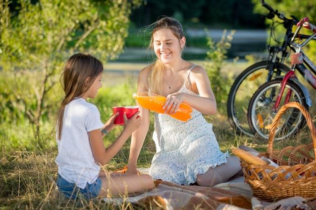 Porträt der jungen mutter, die beim picknick im park saft aus der flasche in die tasse der tochter gießt
