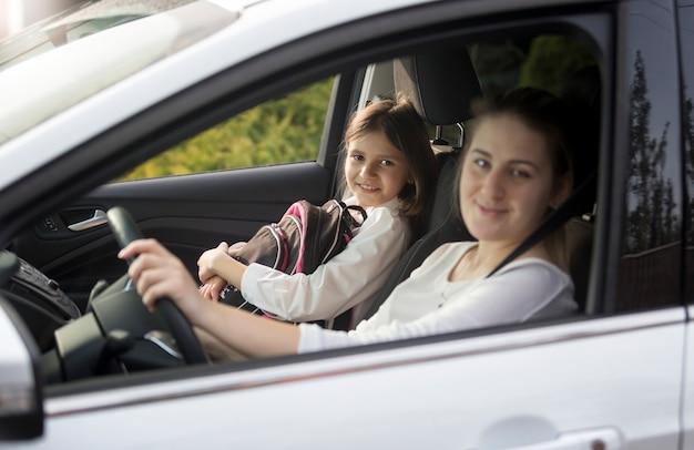 Porträt der jungen mutter, die ihre tochter mit dem auto zur schule bringt