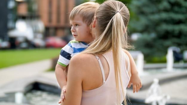 Porträt der jungen mutter, die ihren weinenden kleinkindsohn im park streichelt und beruhigt.