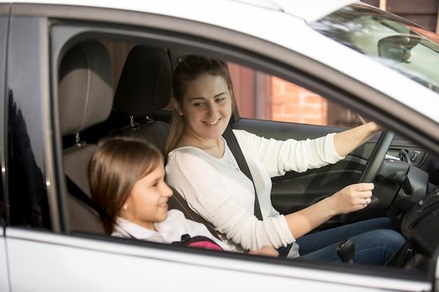 Porträt der jungen mutter, die mit tochter auto zur schule fährt