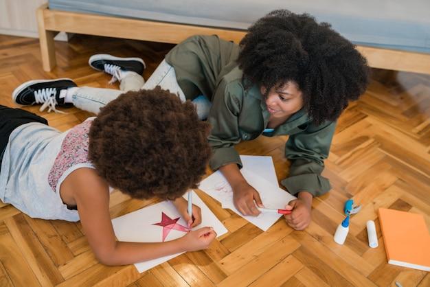 Porträt der jungen mutter und des sohnes, die mit buntstiften auf warmem boden zu hause zeichnen