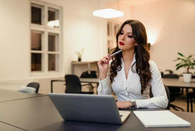 Porträt der jungen nachdenklichen frau, die am schreibtisch vor laptop sitzt.