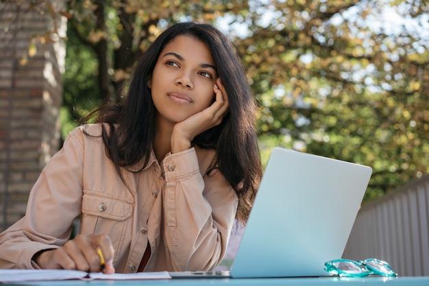 Porträt der jungen nachdenklichen frau unter verwendung des laptops, planen des arbeitsprozesses, sitzen am arbeitsplatz