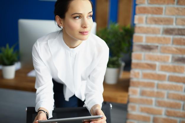 Porträt der jungen nachdenklichen geschäftsfrau mit tablette in den händen im büro. planungskonzept für die geschäftsentwicklung