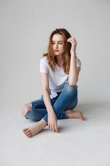 Porträt der jungen nachdenklichen kaukasischen frau, die im t-shirt, blaue zerrissene jeans, auf studioboden sitzend aufwirft.