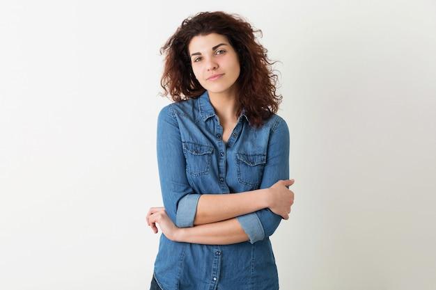 Porträt der jungen natürlichen lächelnden hübschen frau mit der lockigen frisur im jeanshemd, das lokal aufwirft
