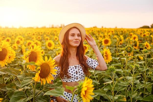 Porträt der jungen netten frau im strohhut draußen auf dem kaukasischen mädchen des sonnenblumenfeldes in ...
