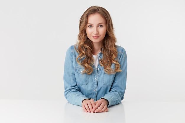 Porträt der jungen niedlichen lockigen blonden dame in jeanshemden, die am weißen tisch sitzen und lächeln, sieht positiv aus, lokalisiert über weißem hintergrund.