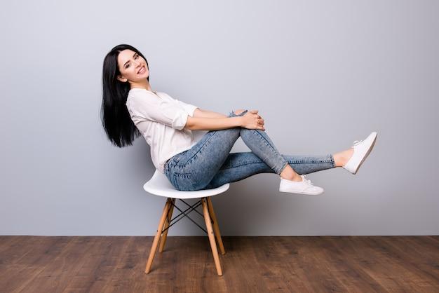 Porträt der jungen niedlichen lustigen frau in den jeans und im weißen hemd lächelnd und posierend auf einem stuhl