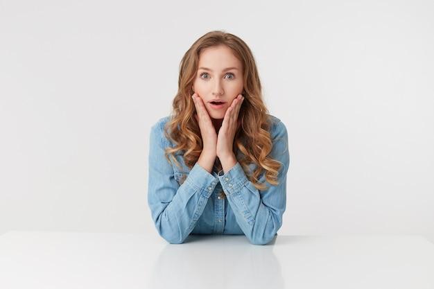 Porträt der jungen niedlichen verwunderten lockigen blonden dame in jeanshemden, die am weißen tisch sitzen und lächeln, sieht überrascht aus, isoliert über weißem hintergrund.
