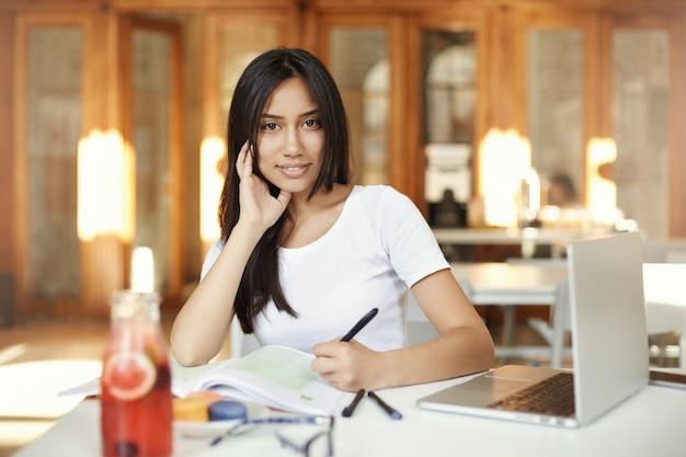 Porträt der jungen östlichen frau, die in einer bibliothek studiert, die limonade trinkt, die an einem laptop arbeitet, der kamera betrachtet.
