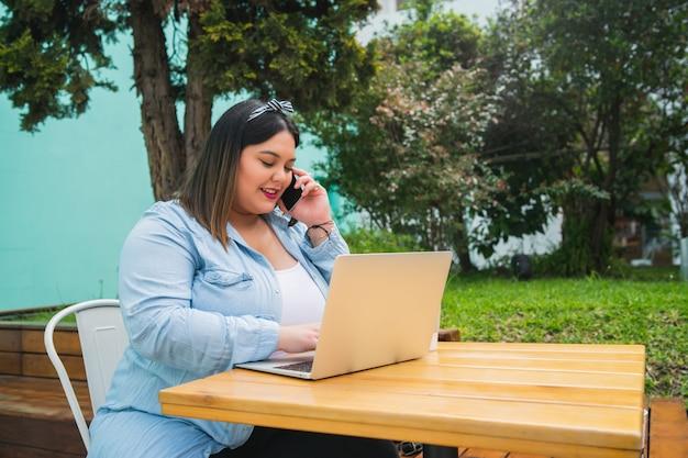 Porträt der jungen pluse größe frau, die ihren laptop benutzt und am telefon spricht, während draußen im café gesessen wird.