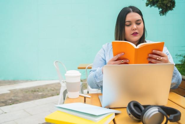 Porträt der jungen pluse größe frau, die mit laptop und büchern studiert, während draußen im café kaufend