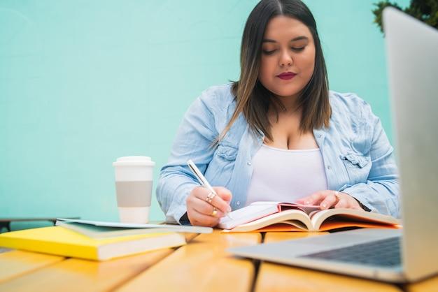 Porträt der jungen pluse größe frau, die mit laptop und büchern studiert, während draußen im café kaufend.