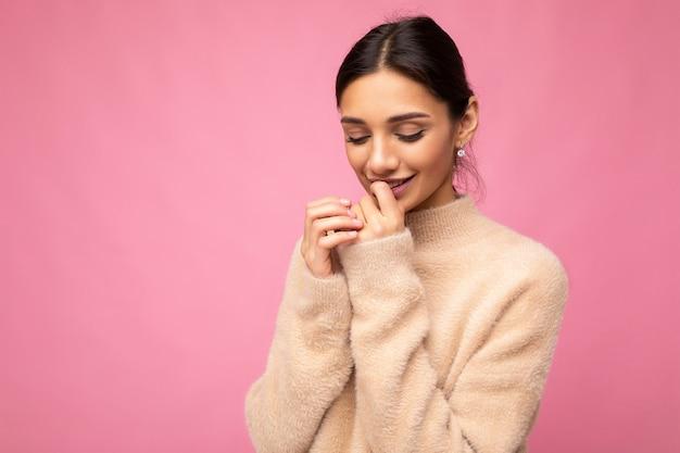 Porträt der jungen positiv lächelnden zarten gewinnenden glücklichen schönen schönen brünetten frau mit aufrichtigen gefühlen, die lässiges beige trikot tragen, isoliert
