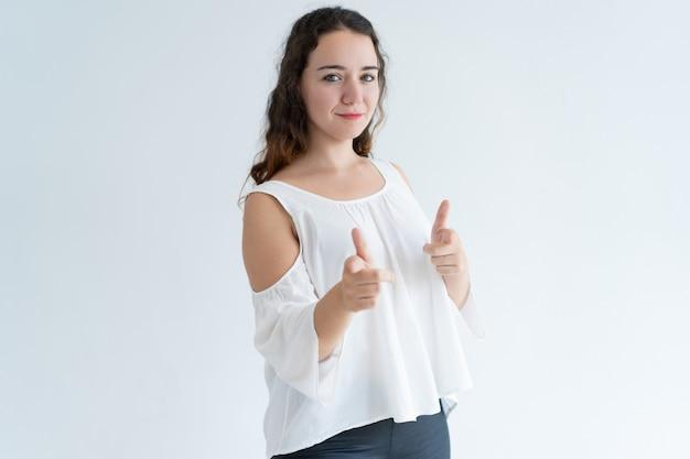 Porträt der jungen positiven frau, die auf die kamera wählt sie zeigt
