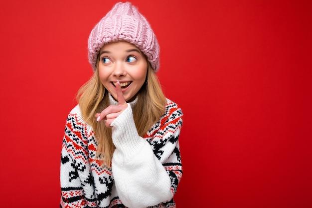 Porträt der jungen positiven glücklichen attraktiven blonden frau mit aufrichtigen gefühlen, die rosa hut trägt und