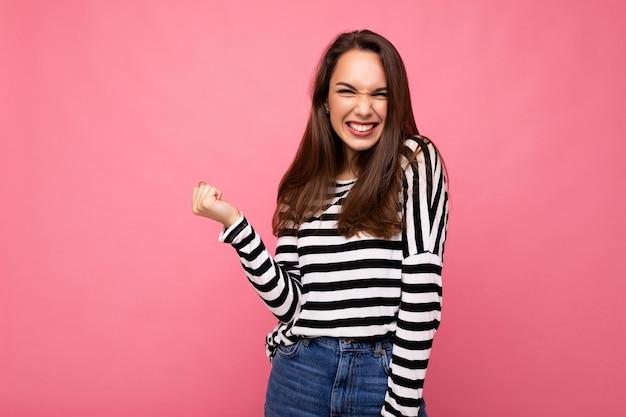 Porträt der jungen positiven glücklichen attraktiven brünetten frau mit aufrichtigen emotionen in lässig gestreift