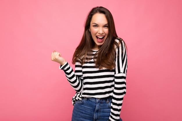 Porträt der jungen positiven glücklichen attraktiven brünetten frau mit aufrichtigen gefühlen, die lässigen gestreiften pullover tragen
