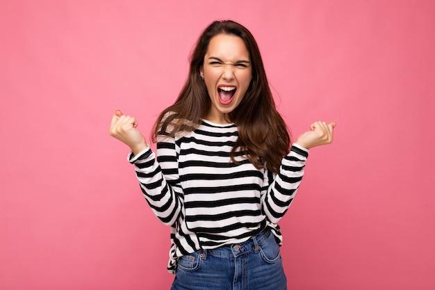 Porträt der jungen positiven glücklichen schönen brünetten frau mit aufrichtigen gefühlen, die beiläufigen gestreiften pullover trägt