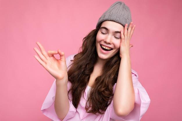 Porträt der jungen positiven glücklichen schönen lockigen brünetten frau mit aufrichtigen gefühlen, die trendy trägt