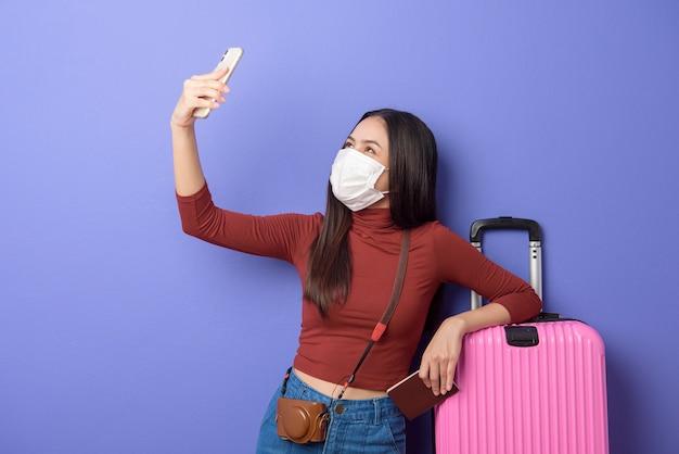 Porträt der jungen reisenden frau mit gesichtsmaske, neues normales reisekonzept
