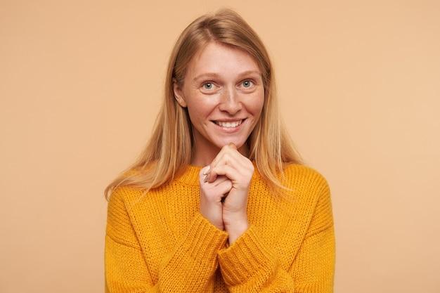 Porträt der jungen reizenden rothaarigen frau mit natürlichem make-up, das mit charmantem lächeln positiv schaut und erhobene hände unter ihrem kinn hält, lokalisiert auf beige