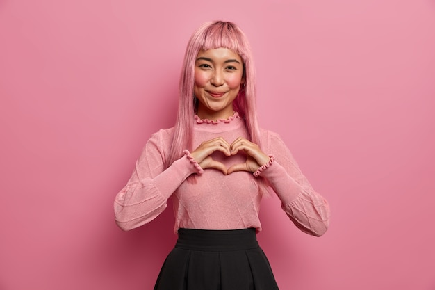 Porträt der jungen romantischen asiatischen frau formt herzgeste zum liebhaber, sendet zuneigung und liebe, drückt sympathie aus, trägt lange rosa perücke