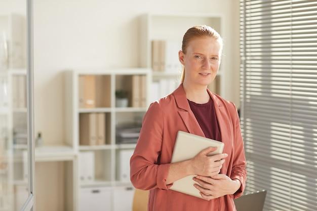 Porträt der jungen rothaarigen geschäftsfrau, die am arbeitsplatz im sonnenbeschienenen büro steht