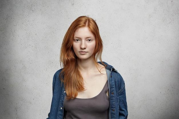 Porträt der jungen rothaarigen kaukasischen frau mit sommersprossen gekleidet im jeanshemd über der spitze, die lokal aussehend ernst oder verärgert aufwirft.