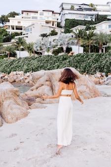 Porträt der jungen ruhigen glücklichen kaukasischen passform schlanke frau in ernte cami top und hosen allein auf felsigen tropischen strand bei sonnenuntergang gesetzt