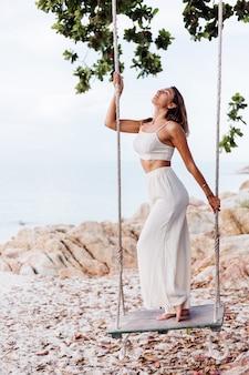 Porträt der jungen ruhigen glücklichen kaukasischen passform schlanke frau in ernte cami top und hosen set sitzt allein auf felsigen tropischen strand bei sonnenuntergang