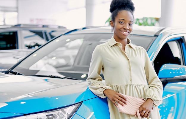 Porträt der jungen schlanken afrikanischen frau, die neben neuem blauen auto steht