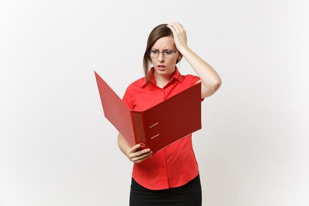 Porträt der jungen schockierten traurigen geschäftslehrerfrau im roten hemd, gläser, die ordner mit den papierarbeitsdokumenten lokalisiert auf weißem hintergrund halten. bildungsunterricht im hochschulkonzept.