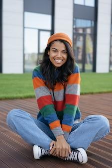 Porträt der jungen schönen afroamerikanerfrau, die draußen sitzt