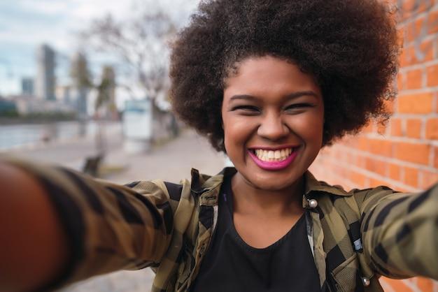 Porträt der jungen schönen afroamerikanischen frau, die ein selfie draußen in der straße nimmt.