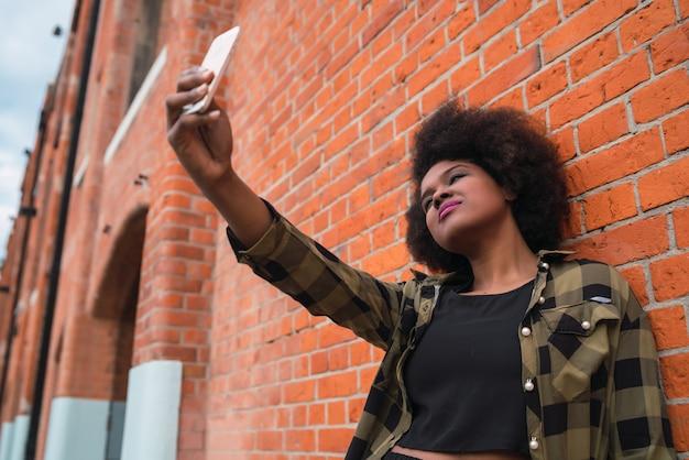 Porträt der jungen schönen afroamerikanischen lateinamerikanischen frau, die ein selfie mit ihrem handy draußen in der straße nimmt.