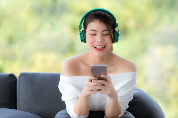 Porträt der jungen schönen asiatin, die auf sofa und hörender musik mit kopfhörer sitzt