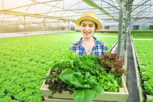 Porträt der jungen schönen asiatin, die frischgemüsesalat von ihrem hölzernen korb und lächeln des hydrokulturbauernhofhandgriffs erntet