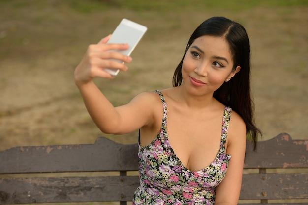 Porträt der jungen schönen asiatischen frau, die am park draußen entspannt