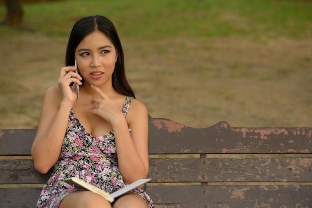 Porträt der jungen schönen asiatischen frau, die am telefon spricht und am park denkt