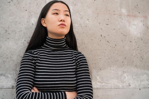 Porträt der jungen schönen asiatischen frau, die draußen gegen graue wand steht.