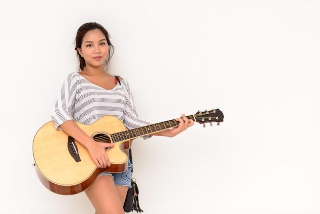 Porträt der jungen schönen asiatischen frau, die draußen gitarre spielt